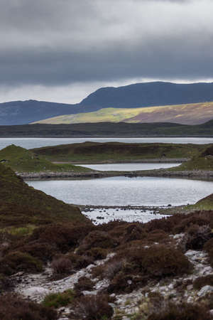 irregularity: Irregularly shaped, gray-water Loch Eriboll under dark cloudy skies. Wide shot showing land tongues, background mountains and green and brown vegetation. Stock Photo