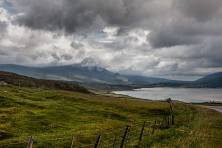 kyle: Northwest Coast, Scotland - June 6, 2012: Kyle of Durness, part of Atlantic Ocean surrounded by mountains. Heavy dark and white rain clouds. Green pasture upfront.