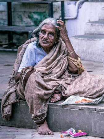 Madurai, India - October 19, 2013: An old graying lady sits on the sidewalk of the street around Meenakshi Temple. She has an expressive dismissing face, scratches her hair and wears a brownish sari. Editorial