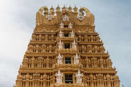 karnataka: Nanjangud, India - October 26, 2013: The elaborately decorated Kalasam and top five levels of the main Gopuram of Sri Srikanteshware temple in Ganjangud, Karnataka State. Golden decoration, white statues. Editorial