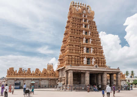 Nanjangud, India - October 26, 2013: The tall beige Gopuram with temple walls and small mandapam in front of the Sri Srikanteshwara Temple in Ganjangud, Karnataka State. A few people on the square in front.