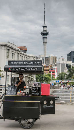 Auckland, New Zealand - March 1, 2017: Tricycle craft coffee shop claiming to be the smallest one in the world. Owner barista. On SymondsWellesley overpass. Sky Tower, high rises and cloudy sky. Editorial