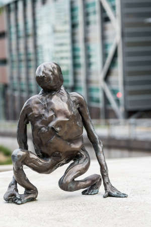 Auckland, New Zealand - March 1, 2017: Overpass Symonds and Wellesley streets. One of public tiny bronze statues, called Loafer, created by Francis Upritchard stands on concrete platform.