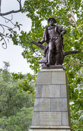 Auckland, New Zealand - March 1, 2017: Full large bronze Robert Burns statue in the Domain Park. Green tree background with gray sky. Editorial