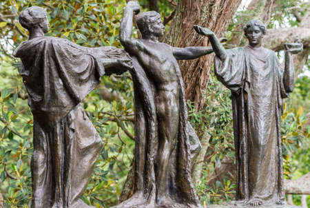 Auckland, New Zealand - March 1, 2017: Three bronze figures represent the male Auckland in the middle of females Wisdom and Fertility. Green tree background. Claims of being haunted gave name. Editorial