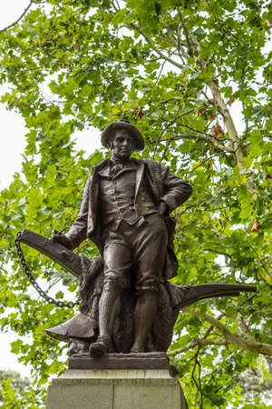 Auckland, New Zealand - March 1, 2017: Closeup of large bronze Robert Burns statue in the Domain Park. Green tree background with some spots of gray sky.