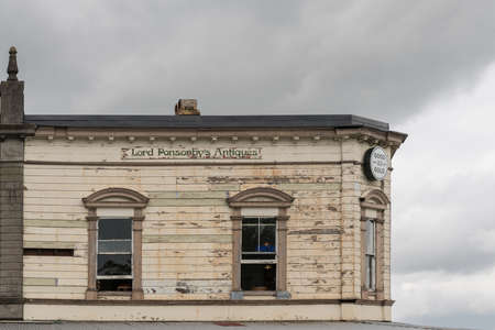 Auckland, New Zealand - March 1, 2017: Dilapidated beige wooden facade of antique shop in Ponsonby Road under dark cloudy skies needs paint and window restorations. Editorial