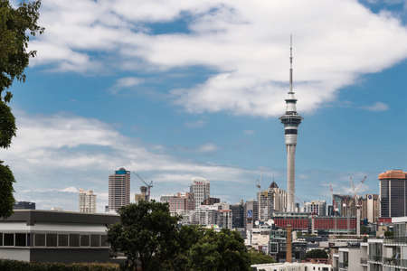 Auckland, New Zealand - March 1, 2017: From the higher lying Ponsonby Road, the Sky Tower can be seen clearly towering over the rest of the skyline with famous business names. White clouds in blue sky Editorial