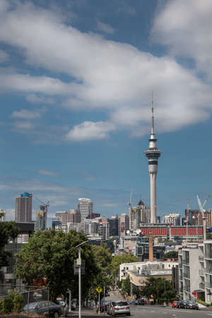 Auckland, New Zealand - March 1, 2017: From the higher lying College Hill, the Sky Tower can be seen clearly towering over the rest of the skyline with famous business names. White clouds in blue sky. Editorial