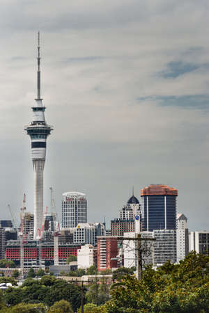Auckland, New Zealand - March 1, 2017: From the higher lying Ponsonby Road, the Sky Tower can be seen clearly towering over the rest of the skyline. White clouds in blue sky.