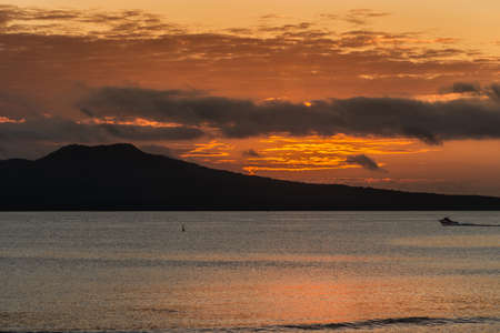 Auckland, New Zealand - March 2, 2017: Sunrise over Rangitoto Volcano, shot from Tapapuna Beach in the Hauraki Gulf. Shot 1 of 4. Fire lines in sky among dark clouds. Black volcano. Blue-gray ocean water reflects orange sky.