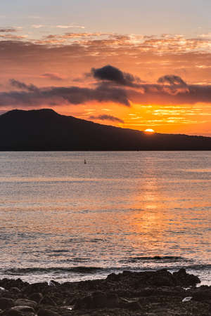 Auckland, New Zealand - March 2, 2017: Sunrise over Rangitoto Volcano, shot from Tapapuna Beach in the Hauraki Gulf. Shot 2 of 4. Half sun, Black volcano. Blue-gray ocean water with orange reflections Stock Photo