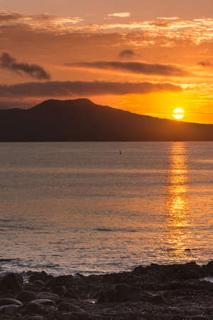 Auckland, New Zealand - March 2, 2017: Sunrise over Rangitoto Volcano, shot from Tapapuna Beach in the Hauraki Gulf. Shot 4 of 4. Full sun, Black volcano. Blue-gray ocean water with orange reflections.