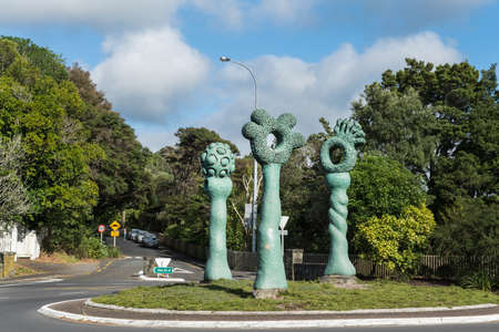 Auckland, New Zealand - March 2, 2017: The green obelisk-like Bush Markers statue on Titirangi roundabout. Green trees under blue sky with white clouds. Street with signs and cars. Editorial