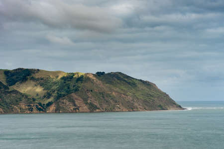 Auckland, New Zealand - March 2, 2017: Manukau Heads at entrance from Tasman Sea into Huia Bay. under heavy cloudscape. Blue-green water. Editorial