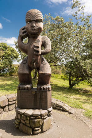 Auckland, New Zealand - March 2, 2017: Wooden sculpture of Te Kawerao A Maki, the spiritual guardian (Manawhenua) of Karakare Beach. Stands on stone footing. Green vegetation in back. Blue sky.
