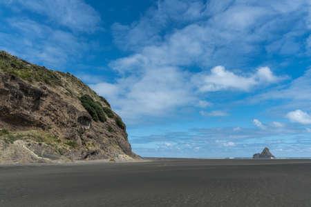 Auckland, New Zealand - March 2, 2017: Wide shot of black sand Karakare Beach under blue cloudy sky with, Te Kaka Whakaara Rock (Watchman) in the surf of Tasman Sea far away. Rocky cliff. Editorial