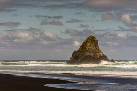 Auckland, New Zealand - March 2, 2017: Black sand Karakare Beach under blue cloudy sky with, Te Kaka Whakaara Rock (Watchman) in the surf of Tasman Sea.