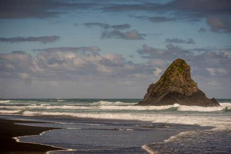 Auckland, New Zealand - March 2, 2017: Black sand Karakare Beach under blue cloudy sky with, Te Kaka Whakaara Rock (Watchman) in the surf of Tasman Sea.