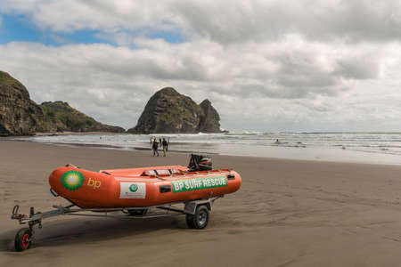 Auckland, New Zealand - March 2, 2017:  Closeup of orange dinghy boat of beach life guard at Piha Beach with Rabbit rock in the back. Tasman sea surf and people.