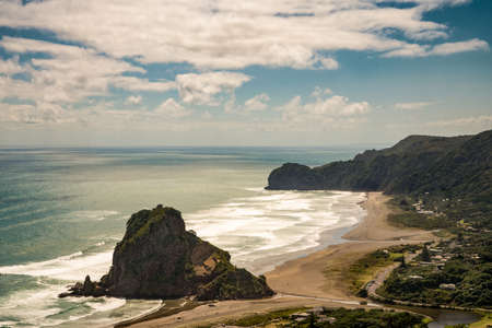 Auckland, New Zealand - March 2, 2017: Aerial view on the Lion rock at sandy Piha Beach under blue sky with white clouds. Tasman Sea surf, forests, cliffs and village.
