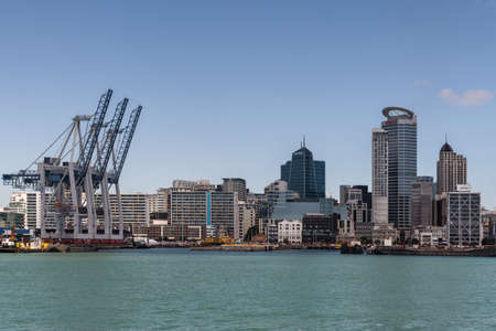 Auckland, New Zealand - March 3, 2017: Row of container cranes at Commercial Harbor with part of city skyline in back under blue sky and behind greenish ocean water. Highrise buildings. No ships.