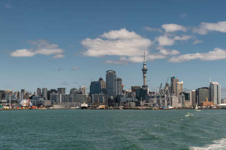 Auckland, New Zealand - March 3, 2017: Wide shot of the city skyline seen from greenish ocean water under blue sky with some white clouds. Highrises, boats and specific buildings.