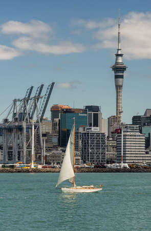 Auckland, New Zealand - March 3, 2017: Portrait of container terminal with its cranes under blue sky and behind greenish ocean water. City skyline with office towers as background. White sailing boat on the water.
