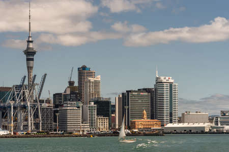 Auckland, New Zealand - March 3, 2017: Container terminal with its cranes under blue sky and behind greenish ocean water. City skyline with ferry terminal and office towers as background. White sailing boat on the water.