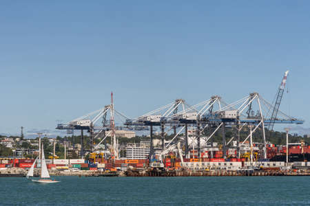 Auckland, New Zealand - March 3, 2017: The container terminal with its cranes and boxes under blue sky and behind greenish ocean water. White sailing boat in front. War Memorial Museum in back.