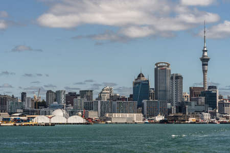 Auckland, New Zealand - March 3, 2017: City skyline seen from greenish ocean water under blue sky with some white clouds. Highrises, Sky Tower and specific office buildings. Editorial