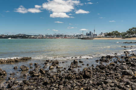Auckland, New Zealand - March 3, 2017: City skyline with With commercial harbor and beyond seen over greenish ocean water under blue sky with some white clouds and shot from Devonport Beach.