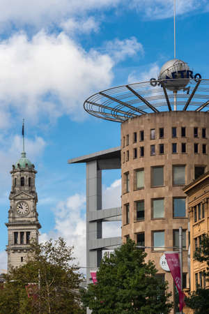 Auckland, New Zealand - March 4, 2017: The brown stone tower of the Metro complex, office and shopping building under blue sky with white clouds. Town Hall Clock Tower in photo with green vegetation.