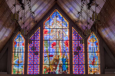 Auckland, New Zealand - March 4, 2017: Mostly blueish large stained glass window at front of Holy Trinity Cathedral features Polynesian and Maori symbols around Christian themes.