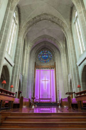 lighted: Auckland, New Zealand - March 4, 2017: Chancel at old part of Holy Trinity Cathedral features wooden benches and altar in front of purple lighted back with large cross. Towering ceiling.