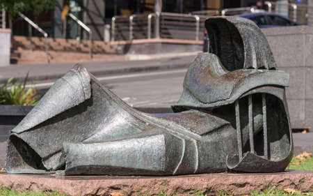 Auckland, New Zealand - March 5, 2017: Closeup of lying empty suit statue in front of Auckland University International House. Gray and rusted metal on red rock.