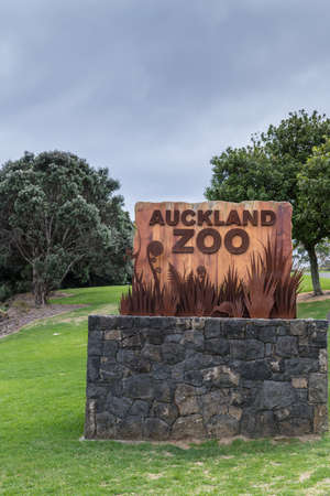 Auckland, New Zealand - March 5, 2017: Rustic colored welcome sign for Auckland Zoo on stone footing in Western Springs Park. Gray-blue skies and green vegetation. Editorial
