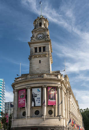Auckland, New Zealand - March 5, 2017: The white stone Clock Tower of town hall with theater posters and flag. Blue sky with white clouds. Editorial