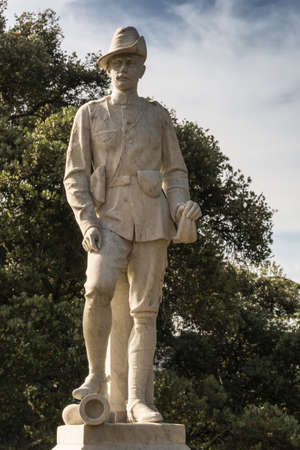 boer: Auckland, New Zealand - March 5, 2017: Closeup of soldier at South African War Artillery Memorial in Albert Park. White stone on pedestal. Green trees in back. Mostly white sky.