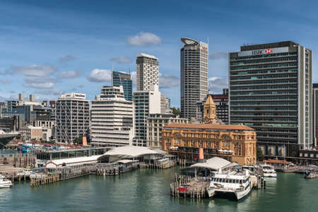 Auckland, New Zealand - March 6, 2017: Ferry building in front of HSBC office building seen from greenish water with a few more high rises in background under blue sky. Ferries at docks.