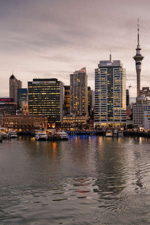 Auckland, New Zealand - March 6, 2017: Ferry building in front of HSBC office building with Sky Tower and a few more high rises in background at sunset. Ferries at docks. Editöryel