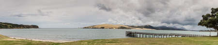 Bay of Islands, New Zealand - March 7, 2017: Panorama shot of exit to Tasman Sea from Hokianga Harbour shows large dune, pier, mountains, all under heavy cloudscape because of approaching cyclone. Stock Photo