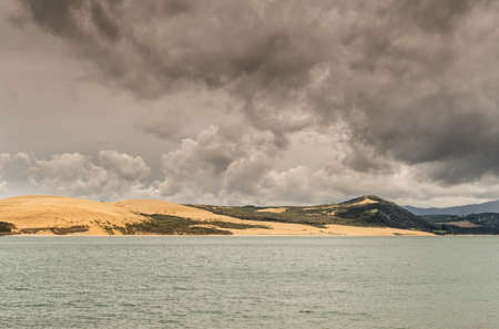Bay of Islands, New Zealand - March 7, 2017: Exit to Tasman Sea from Hokianga Harbour shows large dune under heavy cloudscape because of approaching cyclone.