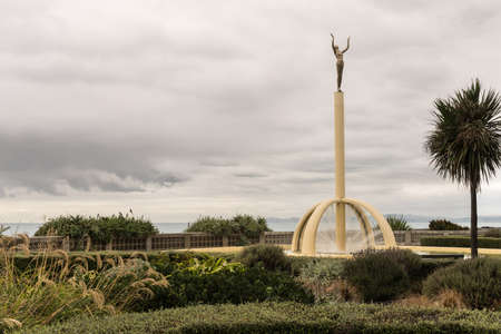 Napier, New Zealand - March 9, 2017: Thomas Gilray O.B.E. Memorial statue and fountain at beach park. Green vegetation up front, Pacific Ocean in back. All under heavy cloudscape. Editorial
