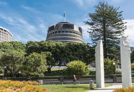 bureaucrat: Wellington, New Zealand - March 10, 2017: Beehive Administrative Government building towers over green vegetation screen. White Maori obelisks and symbols up front. People in photo. Blue sky.