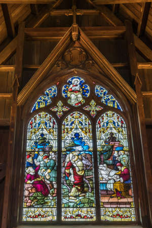 good samaritan: Wellington, New Zealand - March 10, 2017: Inside the wooden Old Saint Paul church shows large elaborate stained glass window in South Alcove depicting three parables of Jesus Christ, New Testament. Editorial