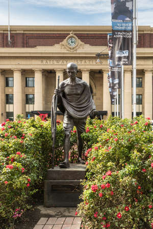 Wellington, New Zealand - March 10, 2017: Classic iconic Mahatma Gandhi bronze statue in front of yellow central railway station with clock. Green bushes with red flowers around the Indian leader.