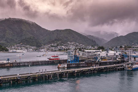 Picton, New Zealand - March 12, 2017: Picton commercial and ferry port with the town in the back on the slope of tall green mountains under heavy brown cloudscape.