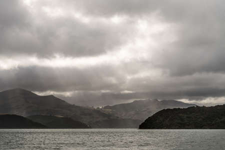 Akaroa Sound is inlet from Pacific ocean in remnants of a Miocene volcano. Heavy rainy cloudscape from water level. Focus on outlet to ocean. Hills and Sun rays.