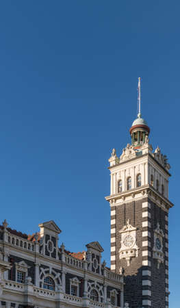 Dunedin, New Zealand - March 15, 2017: Clock tower and part of facade in brown and cream stones of historic railway station against full blue sky.